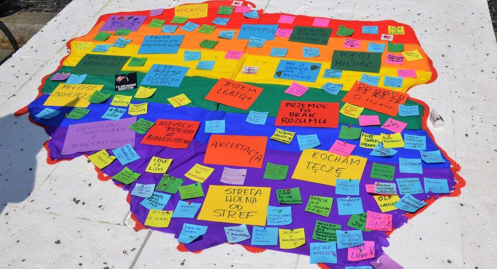Mapa Polski w kolorach tęczy namalowana na styropianie. Przyczepione do niej kolorowe kartki z życzeniami i pozdrowieniami dla uczestników białostockiego Marszu Równości